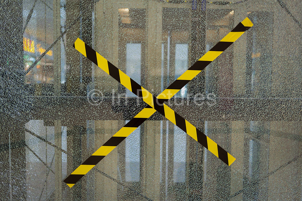 Criss-crossed hazard tape on smashed glass in Vaclav Havel Airport, on 20th March, 2018, in Prague, the Czech Republic.