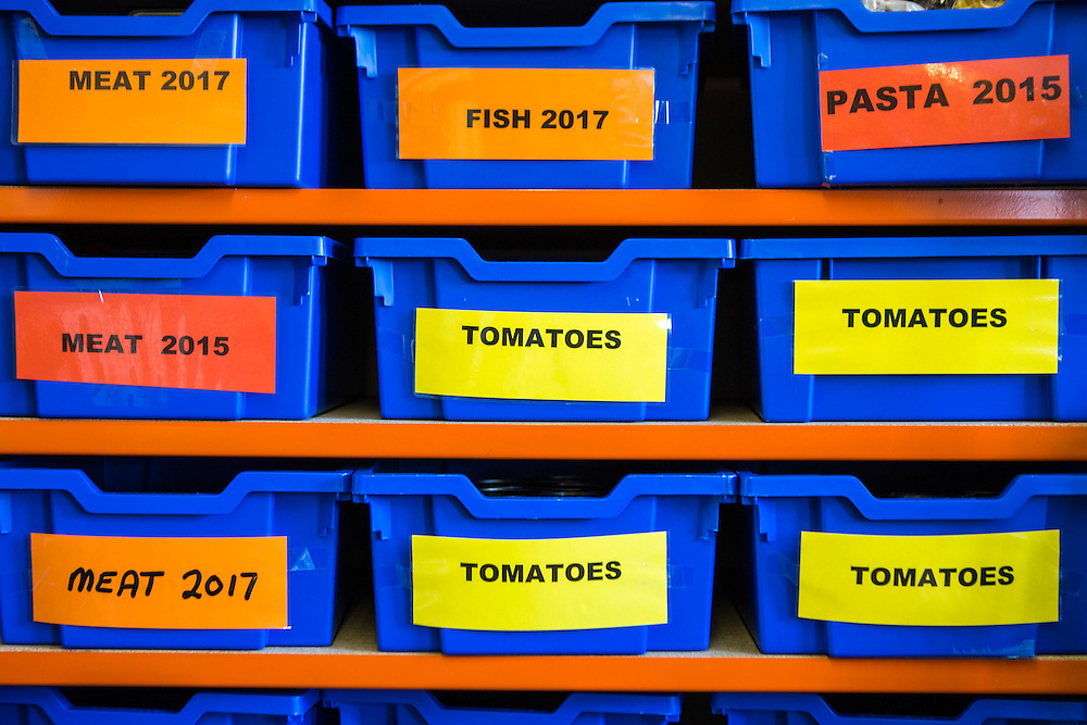 Organized food storage in plastic boxes on shelves in the Trussell Trust foodbank distribution centre in Wadebridge, North Cornwall, United Kingdom. Emergency food boxes are prepared by volunteers and distributed to people in crises.