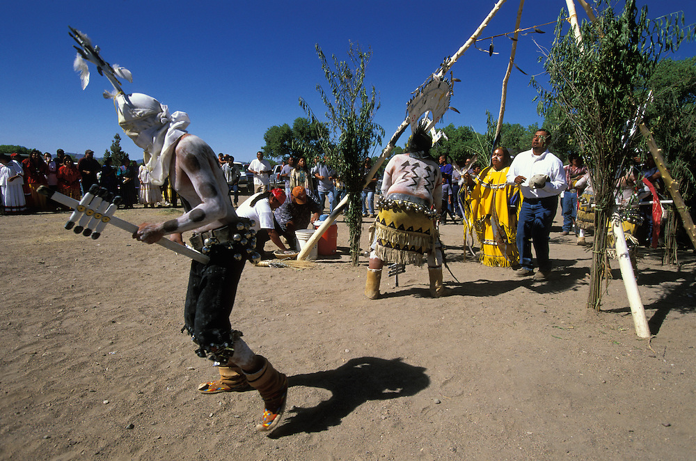 An Apache girl and her godfather dance inside a ceremonial tepee, while mountain spirits (gaan) or crown dancers dance around it, during a Sunrise Dance held on the San Carlos Apache Indian Reservation in Arizona, USA. The Sunrise Dance, the first menstruation rite of an Apache girl, is held during the summer, within one year after the girl has had her first menstruation, and lasts for four days. The ceremony is an enactment of the Apache creation myth and during the rites the girl 'becomes' Changing Woman, a mythical female figure, and comes into possession of her healing powers. The rites are supposed to prepare the girl for adulthood and to give her a long and healthy life without material wants.
