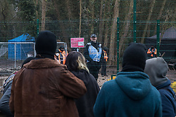 Denham, UK. 7th December, 2020. A Thames Valley Police officer talks to anti-HS2 activists at Denham Ford Protection Camp from a compound to be used by HS2 to bring a bridge across the river Colne and through woodland in Denham Country Park. Activists continue to resist the controversial £106bn high-speed rail project from a series of protest camps based along its initial route between London and Birmingham.