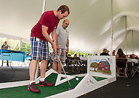 Ron Richard looks on as Matthew Henry chips a shot over the obstacle during NH Ball Bearings barbecue luncheon to honor their employees on Thursday afternoon.  (Karen Bobotas/for the Laconia Daily Sun)