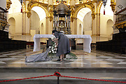 nun cleaning up after arranging flowers in front of altar Cathedral Granada Spain