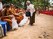 15 MARCH 2015 - SIEM REAP, SIEM REAP, CAMBODIA: A woman makes merit by giving Buddhist monks and novices money at the annual mass merit making at Wat Bo in Siem Reap. More than 1,200 Buddhist monks, from across Siem Reap province, received alms from Buddhist lay people during the morning long ceremony. Wat Bo was originally built to be a the temple for Siamese (Thai) troops when Siem Reap and western Cambodia were controlled by Siam (Thailand). Now Wat Bo is one of the most important temples in Siem Reap.      PHOTO BY JACK KURTZ