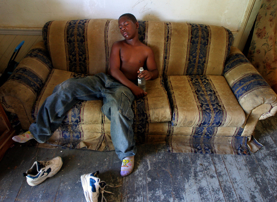 Marvin Wright, rest on the couch in his living room after playing with friends in the front yard. At the time the Wright's did not have running water in their home, which made the bottle of water in his hands something to be thankful for.