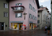 Woman carrying red umbrella walks towartds shop, under large town crucifix in Klausen-Chiusa in the Italian south Tyrol.