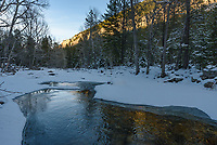 The last light on the cliffs of Piney Creek Canyon is reflected in the cold water.