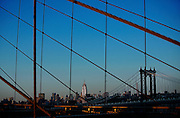 SHOT 3/9/15 4:40:21 PM - The Empire State Building as seen thru some of the cables of the Brooklyn Bridge. The Empire State Building is a 102-story skyscraper located in Midtown Manhattan, New York City, on Fifth Avenue between West 33rd and 34th Streets. It has a roof height of 1,250 feet (380 m), and with its antenna spire included, it stands a total of 1,454 feet (443 m) high. Its name is derived from the nickname for New York, the Empire State. It stood as the world's tallest building for nearly 40 years, from its completion in early 1931 until the topping out of the original World Trade Center's North Tower in late 1970. New York is the most populous city in the United States and the center of one of the most populous urban agglomerations in the world—the New York metropolitan area. The city is referred to as New York City or the City of New York to distinguish it from the State of New York, of which it is a part. A global power city, New York exerts a significant impact upon commerce, finance, media, art, fashion, research, technology, education, and entertainment. New York City has often been described as the cultural and financial capital of the world. (Photo by Marc Piscotty / © 2015)