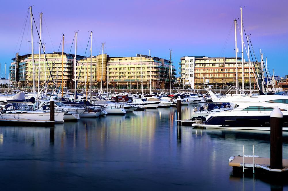 Castle Quay apartments and commercial buildings lit up at dusk along the waterfront, with luxury yachts and sunseekers in the foregound of St Helier harbour, Jersey