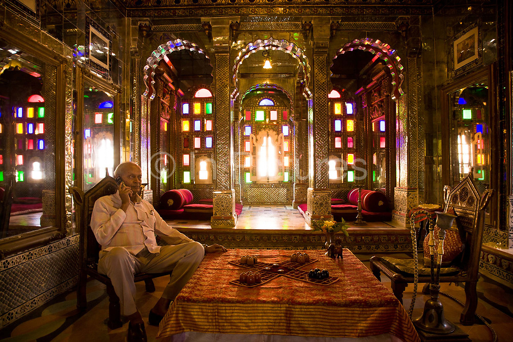 """Nobleman Nahar Singhji, also known as Rao Saheb, sits in the Sheesh Mahal suite of Deogarh Mahal (Fort -Palace) a 340 year old architectural jewel, now converted into  a heritage hotel after the family had no way of maintaining it's upkeep. His family belonged to the Umroa's of Udaipur. """"Lords"""" of the State of Mewar, paying allegiance to the Maharana of Udaipur. Eight generations of his family have lived in the Deogarh fort after which in 1996 it was converted into a hotel, Udaipur, Rajasthan, India"""