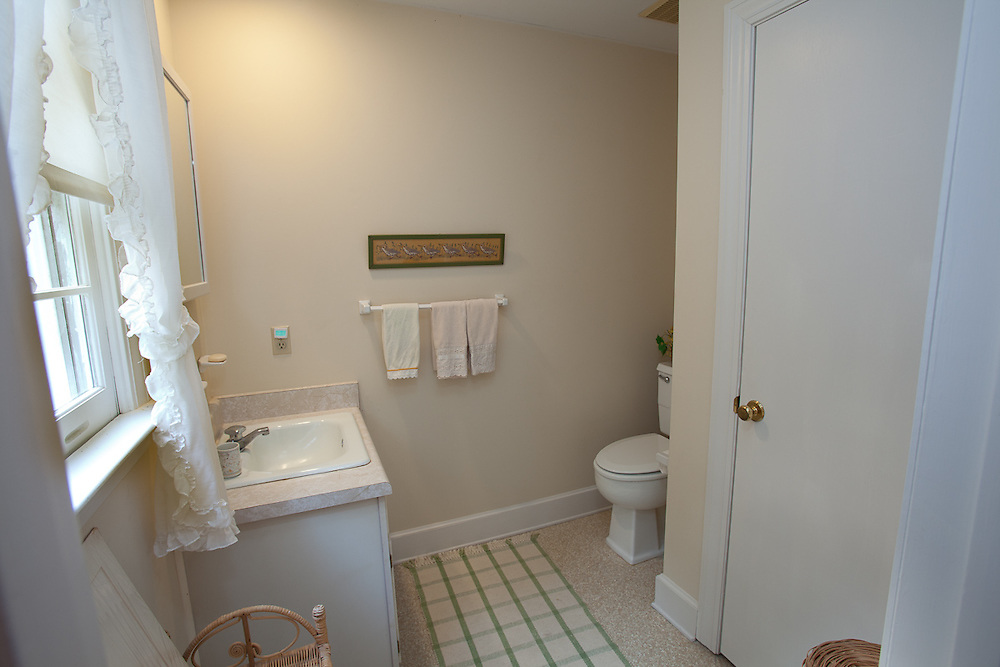 The western upstairs bedroom at 33 Pine View Drive has private half bath.
