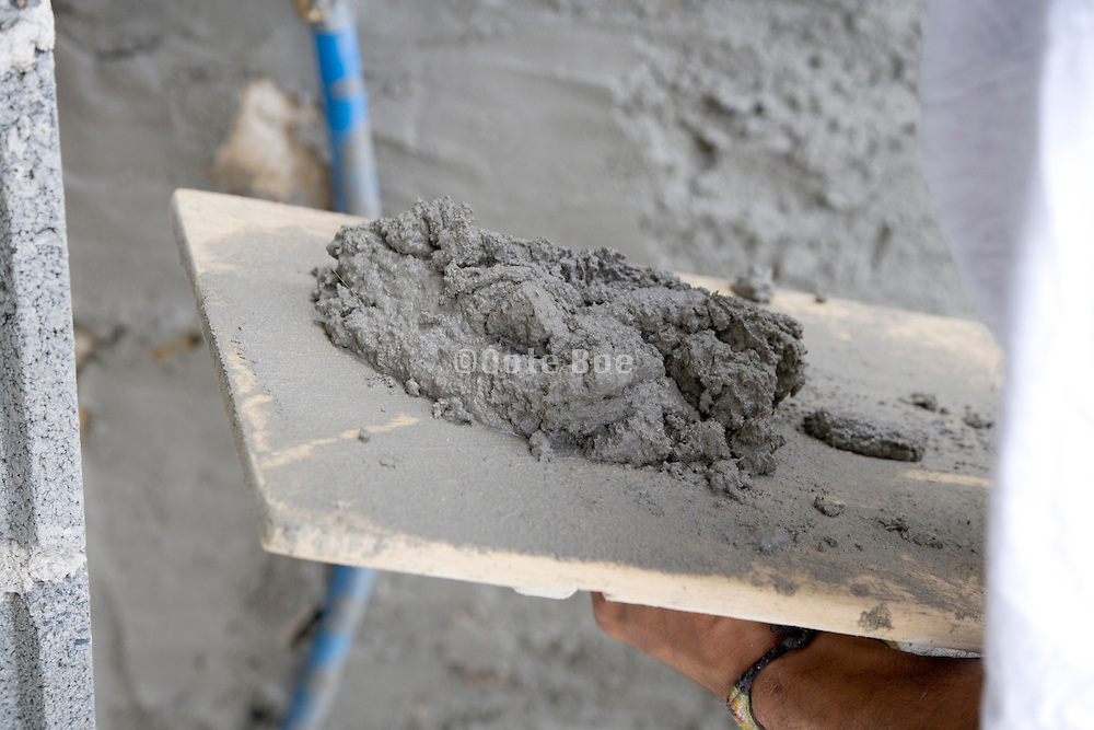 construction worker applying cement coating to a wall