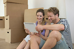Man woman holding tablet computer new home