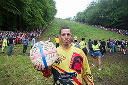 © Licensed to London News Pictures 26/05/2018, brockworth, Gloucester, UK. The annual cheese rolling race held at Coopers Hill, Brockworth outside Gloucester. Competitors race down the extremly steep slippery hill chasing a double Gloucester cheese, the winner of each race recieves the cheese as thier prize. Pictured here :  local legend Chris Anderson with his prize cheese after beating the comprtition to gain his 21st and all time record breaking win - Photo Credit : Stephen Shepherd/LNP