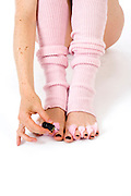 Ofir, Fetish model 26 years old with pink leg wormers doing her tow nails, on white background Model relase available