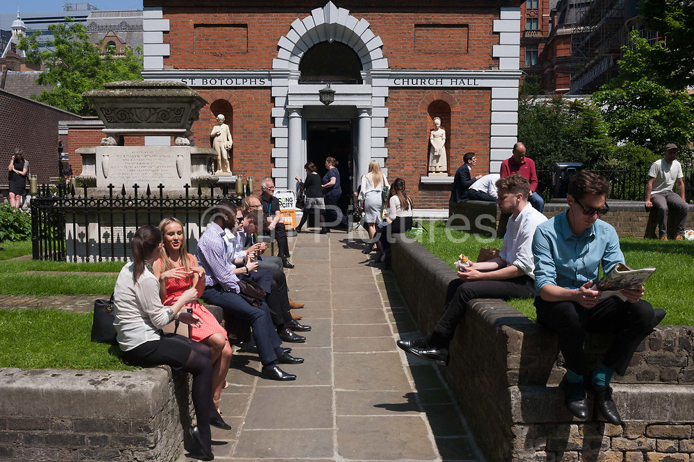 Lunchtime sun for City of London office workers in the grounds of St. Botolph's without Bishopsgate church, on 9th June 2016, in London, United Kingdom. Christian worship has probably been offered at this location at the church of St. Botolph's without Bishopsgate since Roman times. The original Saxon church, the foundations of which were discovered when the present church was erected, is first mentioned as 'Sancti Botolfi Extra Bishopesgate' in 1212. St. Botolph without Bishopsgate may have survived the Great Fire of London unscathed, and only lost one window in the Second World War, but on 24 April 1993 was one of the many buildings to be damaged by an IRA bomb.