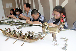 June 14, 2018 - Suzhou, Suzhou, China - Suzhou, CHINA-14th June 2018: The folk artist Xu Rongxing teaches students to make palm fibre weaving of dragon boat shaped artworks at a primary school in Suzhou, east China's Jiangsu Province, June 14th, 2018. (Credit Image: © SIPA Asia via ZUMA Wire)