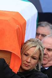 © London News Pictures. 21/03/2017. Derry, UK. Michelle O'Neill carrys the coffin of Martin McGuinness though the streets the Bogside area of Derry, Northern Ireland, 21 March 2017. Sinn Féin's Martin McGuinness, Northern Ireland's former deputy first minister died aged 66 early this morning. It is understood he had been suffering from a rare heart condition. The former IRA leader turned peacemaker worked at the heart of the power-sharing government following the 1998 Good Friday Agreement. He became deputy first minister in 2007, standing alongside Democratic Unionist Party leaders Ian Paisley, Peter Robinson and Arlene Foster.. Photo credit: LNP
