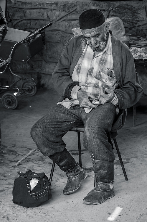 Portrait of an old Tajik man resting on a chair and counting his cash in western Tajikistan