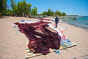 A fisherman tends his nets on the beach in Chizimulu Island, Lake Malawi, Malawi, Africa.