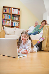 Granddaughter using laptop in living room while grandparents in background