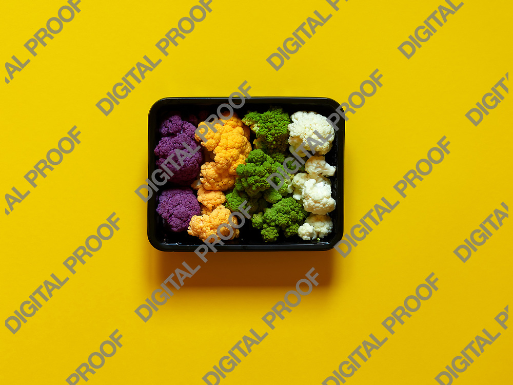 Set of seasonal and colorful cauliflower violet, yellow, green and white boxed in a plastic recipient over a yellow background