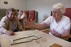 Two elderly women playing game of dominoes at day centre,