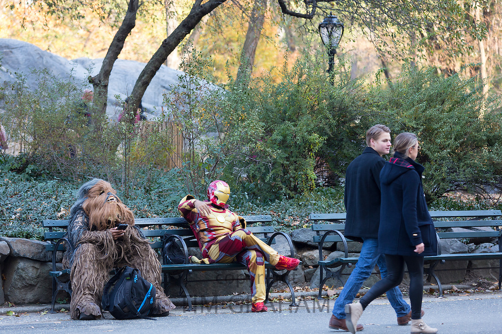 Movie characters in costume chilling out on park bench as couple walk past in winter time in Central Park, New York, USA