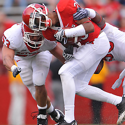 Apr 24, 2010; Piscataway, NJ, USA; Scarlet wide receiver Quron Pratt (28) nearly has his helmet knocked off as he's tackled by White linebackers Antonio Lowery (50) and Jim Dumont (53) and during Rutgers Scarlet and White intersquad NCAA football scrimmage at Rutgers Stadium. The Scarlet squad defeated the White, 16-7.