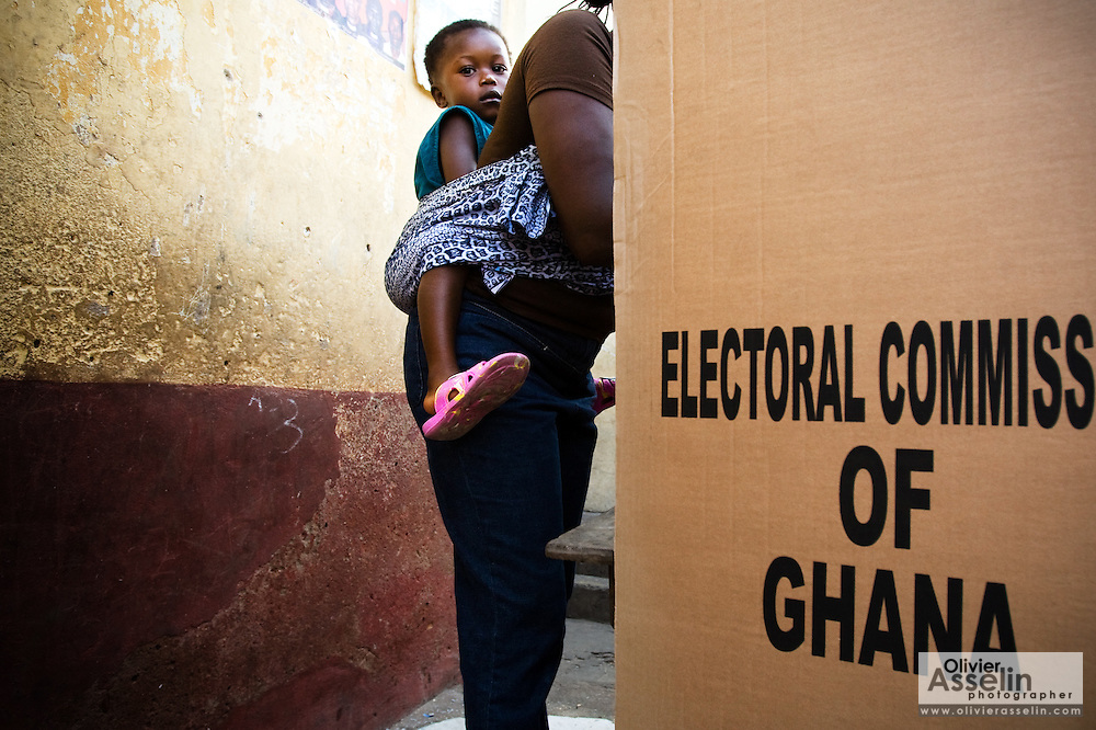 A woman carrying her child on her back votes in a booth during presidential and parliamentary elections in Accra, Ghana on Sunday December 7, 2008.