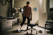 """BIRMINGHAM, AL – FEBRUARY 1, 2019:  Warren """"Azad"""" Stoddard, 24, stands for x-rays that will reveal a bullet fragment lodged in his foot, received while fighting ISIS alongside Kurdish YPG forces in Syria. CREDIT: Bob Miller for The New York Times<br /> <br /> In the war against ISIS, American volunteers have joined the ranks of a Syrian militia, operating independently of the United States. Until recently, the predominantly Kurdish YPG forces had enjoyed air and ground support from the United States, but now that US is officially leaving, the remaining American volunteers face uncertain odds. <br /> <br /> Warren Stoddard, 24, comes from a long line of military veterans and active service members. So when a knee injury prevented him from enlisting in the Marines in 2016, he reached out to a YPG liaison on Facebook to declare his interest in volunteering. """"I always wanted to serve, to do something worthwhile and to take part in some historical event,"""" Stoddard said. """"And I cared about the Kurdish cause."""" Two years later, as the Turkish invasion placed added pressure on the predominantly Kurdish YPG, Stoddard finally received an invitation to join and purchased his own one way ticket. Six months later, while engaging an ISIS stronghold alongside his YPG unit, Stoddard caught bullet fragments in his his upper thigh and foot, where a small fragment is still lodged."""