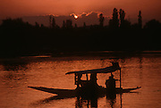 A couple floats in a shikara on Lake Dal in Srinagar, India during sunset.