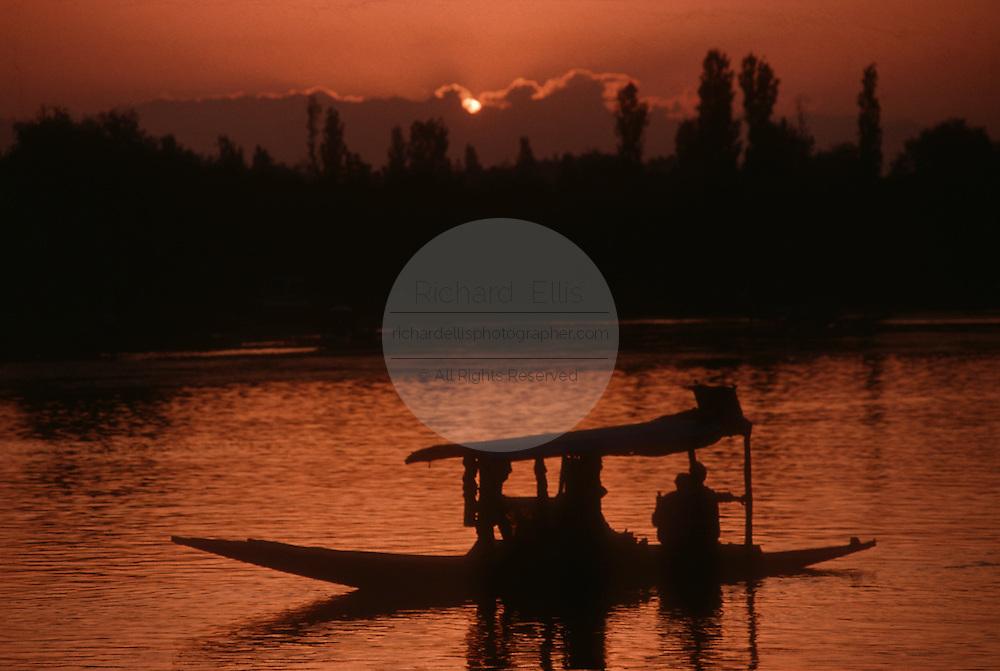 A couple floats in a shikara on Lake Dal in Srinagar, India during sunset.