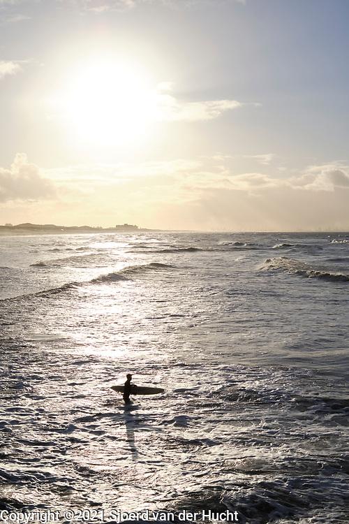 Surfers gaan de zee in. |  Surfers go into the sea