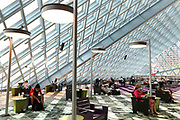 """People read in the """"living room"""" on the third level of the Central Library on the first day of its reopening to the in-person book-browsing public. The branch has three floors open and is one of 13 libraries with air conditioning available for people to cool off from upcoming hot weather. (Ken Lambert / The Seattle Times)"""