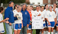 Senior Chelsea Crockett is congratulated by her coaches Eric Porusta and Mark Petrozzi along with her team mates after scoring her 100th career goal during Tuesday's game against Inter Lakes High School.  (Karen Bobotas/for the Laconia Daily Sun)