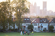 With the tall towers at Nine Elms in the distance, a sun sets below a line of homes and ash trees and a group of friends leave Ruskin Park after a game of cricket, on 13th June 2021, in London, Englnd.