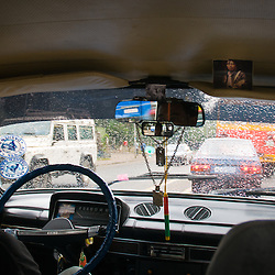 Driving through the busy streets of Addis Ababa in the common blue cab.  The driver displays two photographs of Bob Marley and plays African Reggae on a small radio in the front seat.