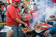 Pro-Chavez demonstrators line up to buy grilled meat for a snack during a demostration in favor of constitutional reforms giving him more power in Caracas, Venezuela in November 2007.