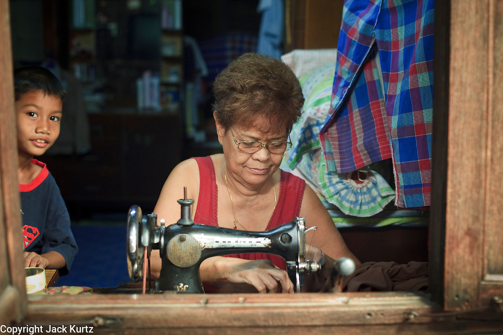 """Mar 23, 2009 -- BANGKOK, THAILAND: A seamstress works in her home in Ban Krua. The Ban Krua neighborhood of Bangkok is the oldest Muslim community in Bangkok. Ban Krua was originally settled by Cham Muslims from Cambodia and Vietnam who fought on the side of the Thai King Rama I. They were given a royal grant of land east of what was then the Thai capitol at the end of the 18th century in return for their military service. The Cham Muslims were originally weavers and what is known as """"Thai Silk"""" was developed by the people in Ban Krua. Several families in the neighborhood still weave in their homes.     Photo by Jack Kurtz"""