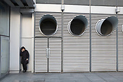 Woman having a cigarette break outside underneath three giant air ducts in London, UK. The large circular vents seem to illlustrate smoking.