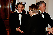British Prime Minister Tony Blair, left, smiles as he shakes hands with Musician Elton John in the receiving line at the State Dinner in his honor February 5, 1998 in Washington, DC. U.S. President Bill Clinton is to the right.