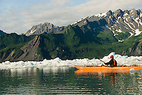 A kayaker paddles in Bear Lake at Bear Glacier, Kenai Fjords National Park, Alaska