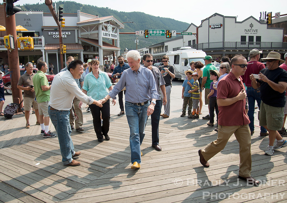 Former President Bill Clinton shakes hands with tourists while walking through downtown Jackson on Sunday afternoon. Clinton shopped at Valley Bookstore and had coffee at Starbucks before leaving the Town Square.