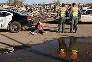 Police surround two men sitting handcuffed on the street suspected of looting in Moore, Oklahoma May 21, 2013. A massive tornado tore through a suburb of Oklahoma City, wiping out whole blocks and killing at least 24.   REUTERS/Rick Wilking (UNITED STATES)