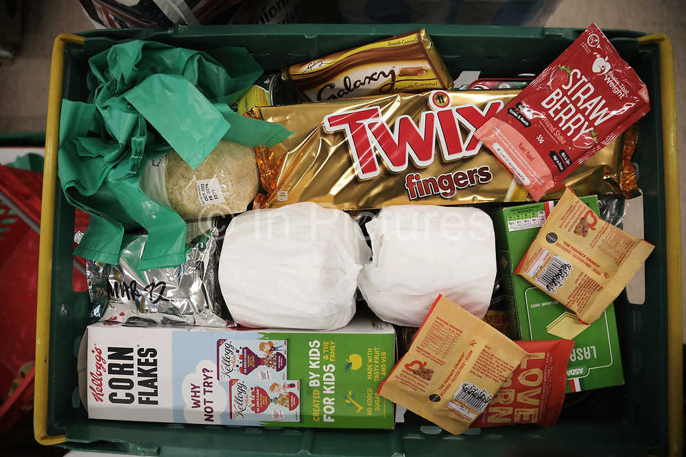 Workers and volunteers at Hackney Foodbank receive and organize food donations, 15th of December 2021, Hackney, East London, United Kingdom. A basket of a family food parcel. The Hackney Food Bank is part of a nationwide network of foodbanks, supported by The Trussell Trust, working to combat poverty and hunger across the UK. The food bank gives out three days emergency food supplies to families and individual who go hungry in the borrough. The food is all donated by individuals and the food donated is held in a small ware house where it is  sorted and packed for distribution.  More people than ever in Britain have turned to the food bank for help and in Hackney the need has gone up with 350% over the past two years.