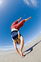 Handstand on beach at Farewell Spit, New Zealand