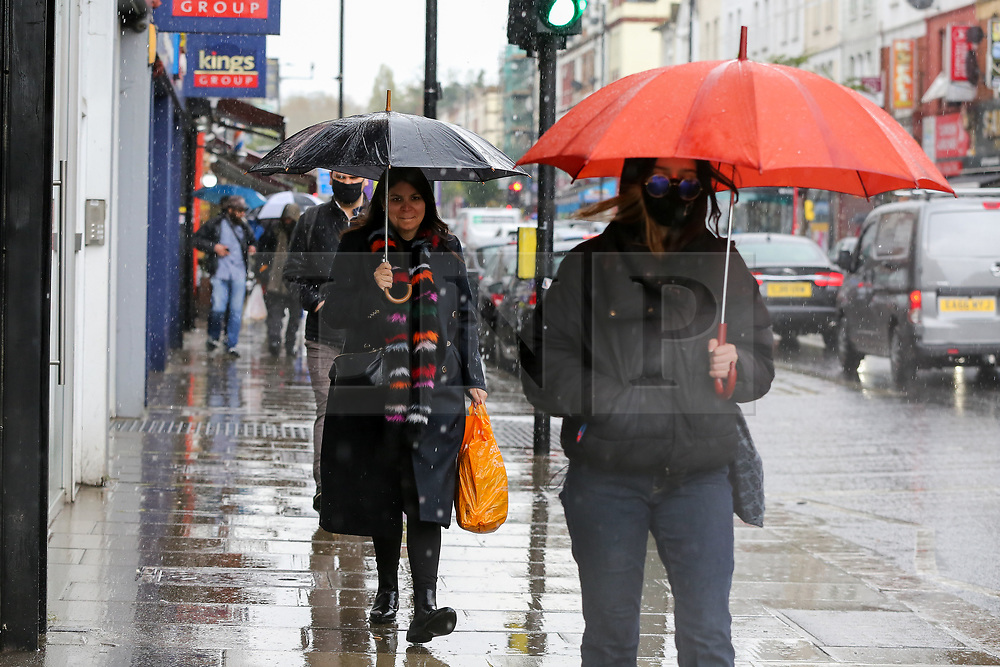 © Licensed to London News Pictures. 02/05/2021. London, UK. Women shelter from heavy rain beneath umbrellas in north London. Windy and wet weather is forecasted for the bank holiday Monday. Photo credit: Dinendra Haria/LNP