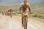 A muddy, smiling Nino Schurter of team SCOTT-Odlo MTB racing leads a bunch up a climb during stage 2 of the 2014 Absa Cape Epic Mountain Bike stage race from Arabella Wines in Robertson, South Africa on the 25 March 2014<br /> <br /> Photo by Greg Beadle/Cape Epic/SPORTZPICS