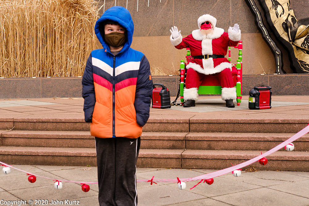 """29 NOVEMBER 2020 - DES MOINES, IOWA: A child poses for a picture with a mask wearing, social distancing Santa Claus during the holiday """"Promenade"""" in the East Village neighborhood of Des Moines. This is the 19th year of the Promenade, a Des Moines tradition that draws shoppers and holiday revelers into the East Village neighborhood. This year's promenade is designed with CDC coronavirus guidelines in place, including social distancing and mask wearing..       PHOTO BY JACK KURTZ"""