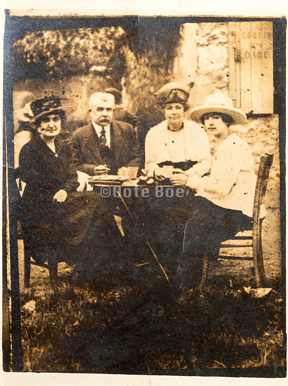 family with friends reposing in the garden France ca 1920s
